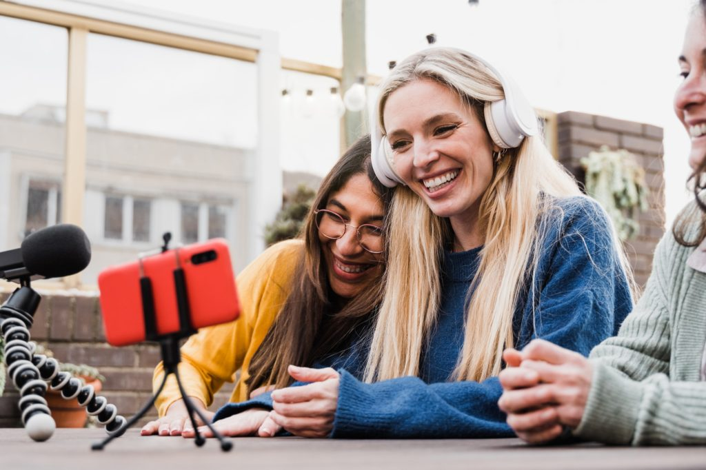 Happy friends streaming online podcast with smartphone outdoors in restaurant